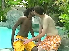 White twink sucks chocolate cock in pool